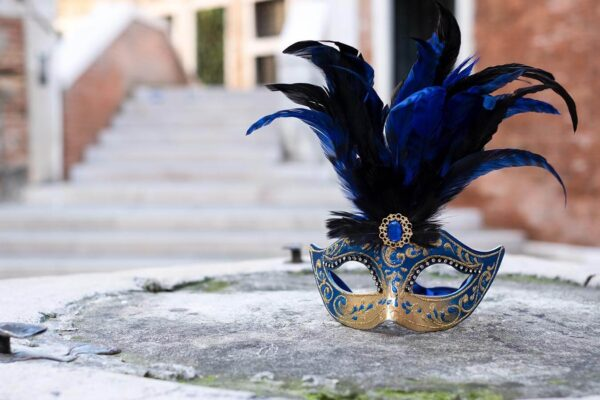 Colombina Mask with feather near a bridge in Venice - Venetian Masks for sale